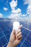 Paneler för sol- energi och ljus kula i handen, energi Royaltyfria Foton