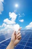 Paneler för sol- energi och ljus kula i handen, energi Royaltyfri Fotografi