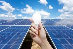 Paneler för sol- energi och ljus kula i handen, energi Fotografering för Bildbyråer