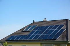Paneler för sol- energi på taket av huset Arkivfoto