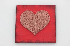 Panels of thread and nails, heart on a red background. string art. gift or decoration for February 14 and March 8. with love stock image
