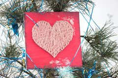 Panels of thread and nails, heart on a red background. string art on a white background in snowand christmas tree . gift or. Panels of thread and nails, heart on royalty free stock photography