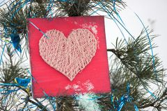 Panels of thread and nails, heart on a red background. string art on a white background in snowand christmas tree . gift or. Panels of thread and nails, heart on royalty free stock photos