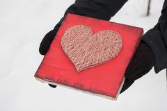Panels of thread and nails, heart on a red background. string art on a white background in the hands. gift or decoration for. Panels of thread and nails, heart royalty free stock images