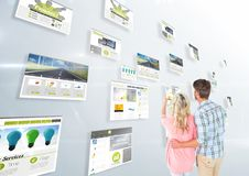 panels with websites(green) , light background and couple looking for them and fingering one Royalty Free Stock Photo