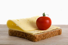 Brödskivan med den körsbärsröda tomaten för ost på trä stiger ombord Royaltyfri Bild
