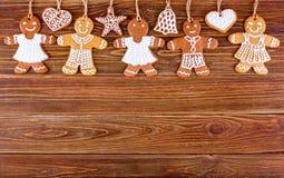 Panes de jengibre hechos en casa de la Navidad con las cuerdas en los tableros de madera Imagenes de archivo