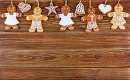 Panes de jengibre hechos en casa de la Navidad con las cuerdas en los tableros de madera Foto de archivo