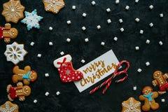 Panes de jengibre de la Navidad, melcochas y tarjeta de felicitación fotos de archivo