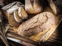 Panes del pan negro en el tablón de madera imágenes de archivo libres de regalías