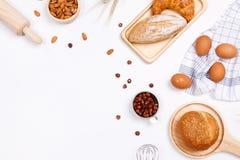 Panes hechos en casa o ingredientes del bollo, del cruasán y de la panadería, harina, nueces de la almendra, avellanas, huevos en foto de archivo