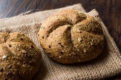Panes redondos recientemente cocidos del rollo de Kaiser del grano del trigo integral con el saco fotografía de archivo