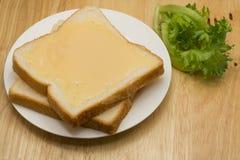 Panes y leche condensada azucarada en una placa blanca Foto de archivo libre de regalías