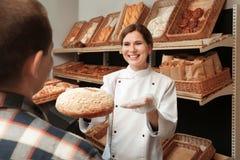 Panettiere che dà a cliente pane fresco fotografie stock libere da diritti