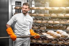Panettiere che mette con le pagnotte del pane della pala alla fabbricazione immagine stock libera da diritti