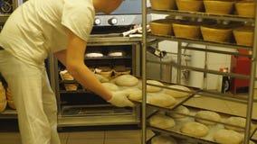 Panettiere che prende una pagnotta di pane di recente al forno dal forno in un forno moderno archivi video
