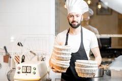 Panettiere con le forme di cottura al forno fotografia stock