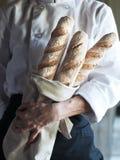 Cuoco unico con le baguette fresche Immagini Stock Libere da Diritti