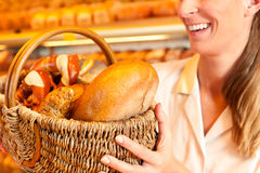 Panettiere femminile che vende pane dal canestro in forno Fotografie Stock