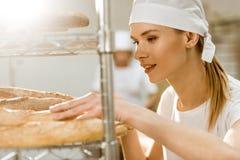 panettiere femminile giovane che fa esame delle pagnotte di recente al forno del pane Fotografia Stock