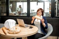Panettiere senior della donna che controlla qualità del pane immagine stock