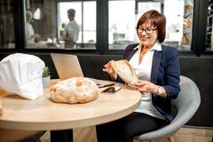 Panettiere senior della donna che controlla qualità del pane immagine stock libera da diritti