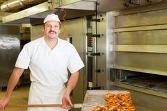 Panettiere in suo pane di cottura del forno Fotografie Stock