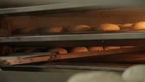 panettiere in uniforme che elimina di recente con il pane al forno del buckweat della pala dal forno alla fabbricazione archivi video