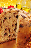 Panettone and champagne. Closeup of a panettone, a typical Italian sweet for Christmas time, on a set table with some glasses with champagne in the background Stock Photography