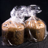 Panettone Christmas bread. Two loaves of Italian panettone Christmas bread wrapped in plastic bags, on a black background royalty free stock photography