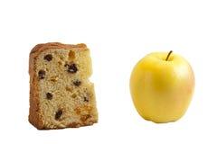 Panettone gegen frischen Apfel Stockbild