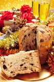 Panettone, gifts and champagne. Closeup of a panettone, a typical Italian sweet for Christmas time, on a set table with some glasses with champagne and some Royalty Free Stock Images