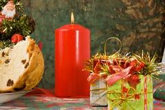 Panettone - Italian xmas cake. Traditional Italian Christmas cake Panettone with xmas candle, tree and gifts Royalty Free Stock Photography