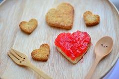Panez la coupe et la confiture de fraise rouge dans la forme du coeur et du woode image libre de droits