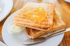 Panez le pain grillé avec la confiture d'oranges, la crème et le service en acier de couteau dessus photo stock