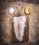 Pangasius brut sur une planche à découper avec la fin rustique en bois de vue supérieure de fond de beurre et de sel  photo libre de droits