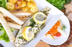 Pangasius fillet in herb crust with asparagus in brown butter Royalty Free Stock Photography