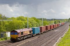 Class 66 diesel intermodal freight train. Pangbourne, UK - MAY 19: A DBS operated intermodal freight train passes under the recently installed electrification Royalty Free Stock Image