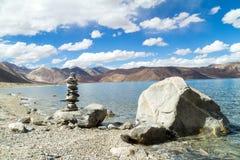 Pangong Tso mountain lake panorama with rocks in forefront Stock Image