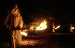 Panhandle, Florida, United States - circa 1995 - Ku Klux Klan KKK Night Ceremony Members in White Robes, Hoods burning torches. Ku Klux Klan Night Rally Members Royalty Free Stock Photo