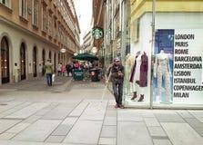 Panhandler die zich naast een manieropslag bevindt Royalty-vrije Stock Afbeeldingen