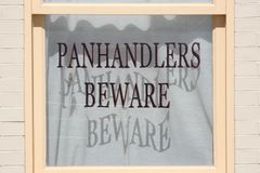 Panhandlers Beware. A window with the sign: Panhandlers Beware royalty free stock photography