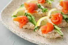 Pani croccanti con il raccordo di color salmone affettato fresco sul piatto Fotografia Stock