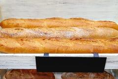 Pani liberi delle baguette del glutine di recente al forno sugli scaffali di legno bianchi immagine stock libera da diritti