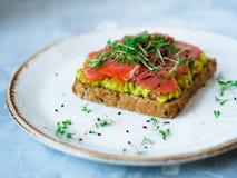 Pani tostati casalinghi con l'avocado ed il salmone affumicato, spruzzati con crescione e sesamo nero Fotografia Stock Libera da Diritti