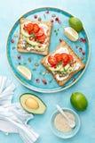Pani tostati con feta, i pomodori, l'avocado, il melograno, i semi di zucca ed i germogli del seme di lino Prima colazione di die immagine stock libera da diritti