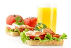 Pani tostati con i tagli freddi su ora di pranzo con succo d'arancia su bianco immagini stock libere da diritti