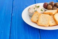 Pani tostati con il patè e le olive del pesce sul piatto Fotografia Stock Libera da Diritti