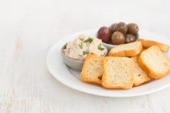 Pani tostati con il patè e le olive del pesce sul piatto Immagine Stock Libera da Diritti