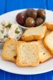 Pani tostati con il patè e le olive del pesce sul piatto Fotografia Stock